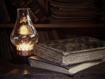 Alte Bücher auf einem Holztisch, antike Lampe Stockfotografie