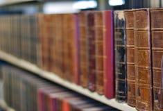 Alte Bücher auf einem Regal an der Bibliothek Stockbilder