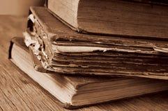 Alte Bücher auf einem rustikalen Holztisch, Sepiatonen Lizenzfreie Stockfotos