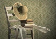 Alte Bücher auf einem Stuhl mit Strohhut Lizenzfreies Stockbild