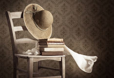 Alte Bücher auf einem Stuhl mit Strohhut Lizenzfreie Stockbilder