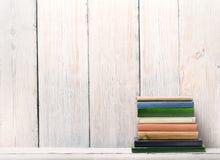 Alte Bücher auf hölzernem Regal, Dorn-Abdeckung über weißer hölzerner Wand Lizenzfreie Stockfotos