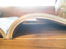 Alte Bücher auf hölzerner Plattformtabelle und Fenstern Hintergrund, L Stockfoto