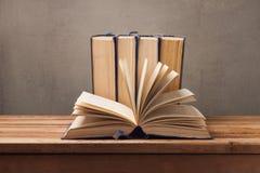 Alte Bücher auf Holztisch über rustikalem Hintergrund getrennte alte Bücher Stockfotografie