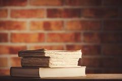 Alte Bücher auf Holztisch an der Backsteinmauer Lizenzfreie Stockfotos