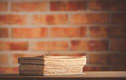 Alte Bücher auf Holztisch an der Backsteinmauer Lizenzfreie Stockbilder