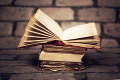 Alte Bücher auf Schmutzwandhintergrund Stockfotografie