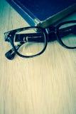 Alte Bücher der Brillen und der Weinlese auf hölzernem Lizenzfreie Stockfotos