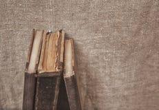 Alte Bücher der Weinlese auf dem alten Leinwandgewebe Stockfotos
