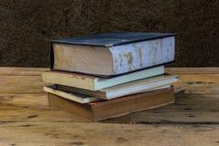 Alte Bücher der Weinlese auf hölzerner Plattformtabelle mit Bodenwand Lizenzfreies Stockbild