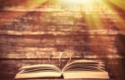Alte Bücher der Weinlese mit Herzen formen auf Holztisch Lizenzfreie Stockbilder