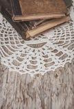 Alte Bücher der Weinlese und Spitzegewebe auf dem alten Holz Stockbilder