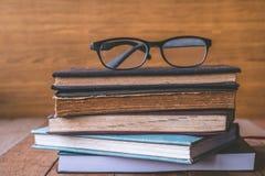 Alte Bücher des gebundenen Buches mit Gläsern auf Holztisch Lizenzfreies Stockfoto