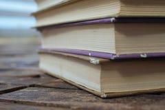 Alte Bücher des Stapels auf hölzernem Hintergrund Stockfotos