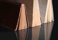 Alte Bücher, die auf reflektierender Oberfläche stehen Lizenzfreies Stockbild