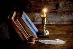 Alte Bücher, ein Stift und eine brennende Kerze Lizenzfreies Stockbild