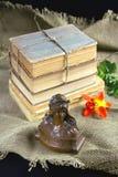 Alte Bücher, eine Blume und ein Bronzefehlschlag Stockbild