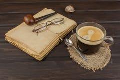 Alte Bücher, Eyewear und Tasse Kaffee auf einem dunklen Holztisch Altes Buch und Kaffee der Leseweinlese Stockbild