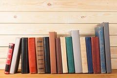 Alte Bücher in Folge auf hölzernem Hintergrund Stockfotos