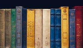 Alte Bücher in Folge in der Bibliothek auf schwarzem Hintergrund mit Kopie-Raum Stockbild