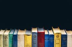 Alte Bücher in Folge in der Bibliothek auf schwarzem Hintergrund mit Kopie-Raum Lizenzfreie Stockfotografie