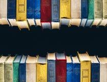 Alte Bücher in Folge in der Bibliothek auf schwarzem Hintergrund mit Mittelkopie-raum Lizenzfreie Stockfotos