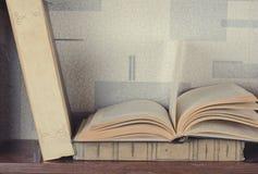 Alte Bücher gelegt auf ein hölzernes Regal Stockfoto