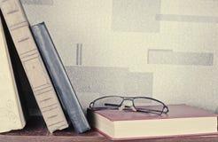 Alte Bücher gelegt auf ein hölzernes Regal Stockbild