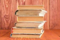 Alte Bücher gestapelt auf hölzernem Beschaffenheitshintergrund Lizenzfreies Stockbild