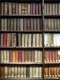 alte Bücher gestapelt auf hölzernen Regalen Stockfotos