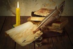 Alte Bücher, Kerze und Feder mit Tinten Stockfotografie