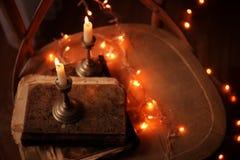 Alte Bücher, Kerzen und Girlande auf Holzstuhl, Lizenzfreies Stockbild