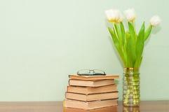 Alte Bücher mit einem Blumenstrauß von Tulpen auf einem Holztisch Stockbilder