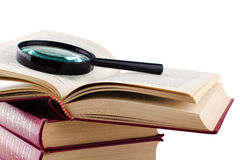 Alte Bücher mit einer Lupe auf weißem Hintergrund. Stockfotos