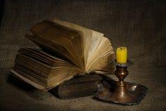 Alte Bücher mit gelber Kerze auf Segeltuchhintergrund Stockfotos