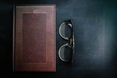 Alte Bücher mit Gläsern auf einem schwarzen Hintergrund Lizenzfreie Stockfotografie