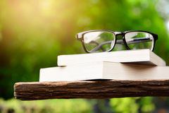 Alte Bücher mit Gläsern auf einer Tabelle Stockfotografie