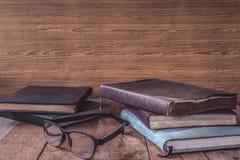 Alte Bücher mit Gläsern auf Holztisch Freier Platz für Text Stockbilder