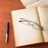Alte Bücher mit Gläsern und Feder Stockfotografie