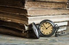 Alte Bücher mit Tasche stoppen auf einem Holztisch ab Stockfotos