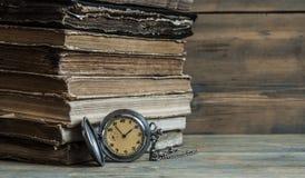 Alte Bücher mit Tasche stoppen auf einem Holztisch ab Stockfotografie