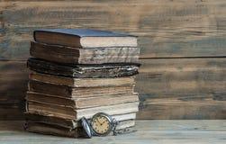 Alte Bücher mit Tasche stoppen auf einem Holztisch ab Stockbilder