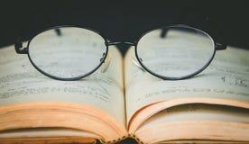 Alte Bücher mit Weinlesegläsern auf einem Holztisch Lizenzfreies Stockbild