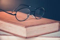 Alte Bücher mit Weinlesegläsern auf einem Holztisch Stockbild