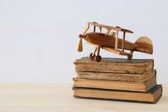 alte Bücher nahe bei flachem Spielzeug auf Holztisch Lizenzfreie Stockfotos