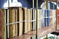 Alte Bücher oben gebunden mit Seil auf Regal Stockfoto
