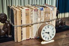 Alte Bücher oben gebunden mit Seil und Wecker Stockbilder