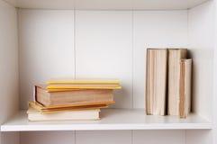 Alte Bücher oder Lehrbücher auf hölzernem Bücherregal Lizenzfreie Stockfotos