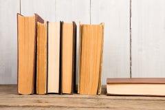 Alte Bücher oder Lehrbücher des gebundenen Buches auf hölzernem Hintergrund Lizenzfreies Stockbild