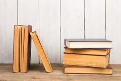 Alte Bücher oder Lehrbücher des gebundenen Buches auf hölzernem Hintergrund Stockfotos